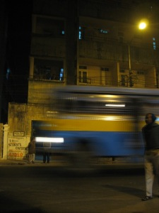Ein Bus prescht nachts durch eine Strasse in Kalkutta